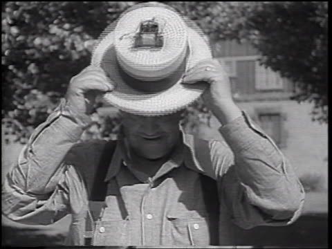 b/w 1937 man with suspenders looking at camera placing straw hat with motor + wires on head - straw hat stock videos & royalty-free footage