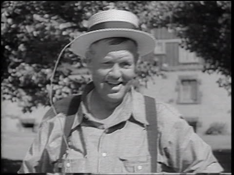 b/w 1937 portrait man with suspenders removing straw hat with attached wire - only mature men stock videos & royalty-free footage