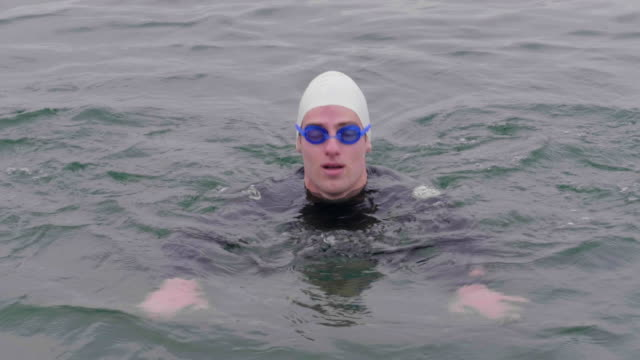 man with swimming hat and goggles swimming towards the camera - continuity stock videos and b-roll footage