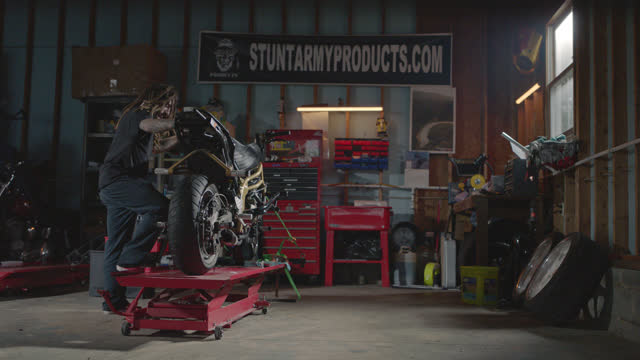 man with tattoos and dreadlocks jacks stunt motorcycle up on hydraulic lift in garage repair shop. - customised stock videos & royalty-free footage