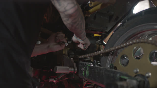 man with tattoos and dreadlocks works on stunt motorcycle with tools in garage repair shop. - motorcycle biker stock videos & royalty-free footage