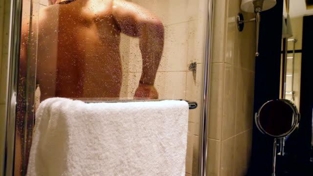 vídeos de stock e filmes b-roll de man with tattoos having a shower - homem tomando banho