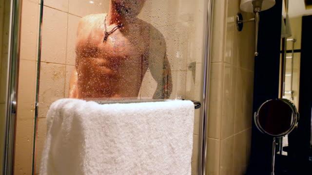 vidéos et rushes de homme tatoué ayant une douche - tatouage