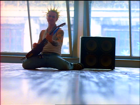 Man with tattoos + spiked hair playing guitar on knees in studio next to amplifier