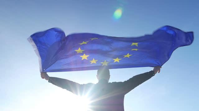 stockvideo's en b-roll-footage met een mens met de europese vlag enia die in de wind wordt uitgestrekt - politiek en staatsbestuur