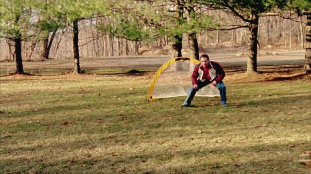 vídeos y material grabado en eventos de stock de ms, man with three children (12-13, 14-15) playing soccer, orangeburg, new york, usa - hacer un gol
