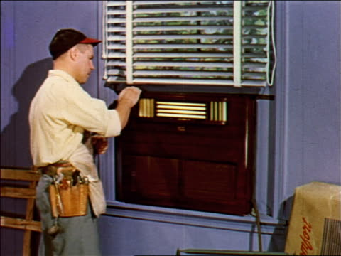 1955 man with tool belt installing air conditioner in window / industrial - tool belt stock videos and b-roll footage