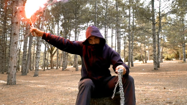 vídeos de stock e filmes b-roll de man with torch and chain sitting in forest - bandido