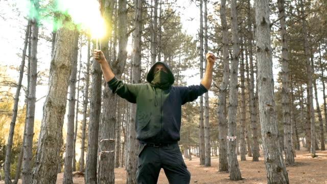 vídeos de stock e filmes b-roll de man with torch in forest - bandido
