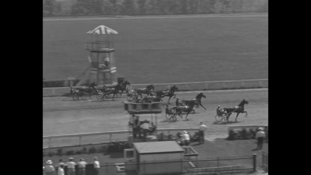SOT man with tote board takes bets from people at trials for Hambletonian horse race he gives odds for Greyhound / horses run in harness race at...