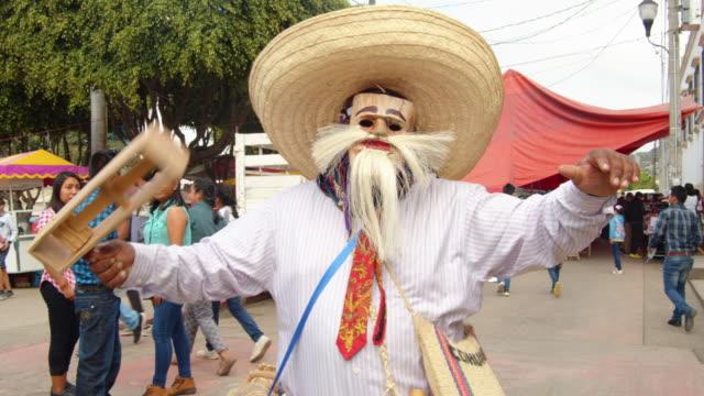 man with traditional costume and carraca noisemaker. mexican carnival from chiapas. zoque coiteco at ocozocoautla de espinosa - traditionelles fest stock-videos und b-roll-filmmaterial