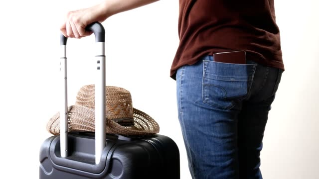 man with travel luggage and hat put his passport into jeans back pocket to prepare for traveling