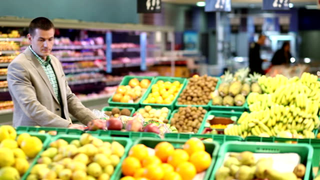 man with trolley by fruit counter in supermarket - apple fruit stock videos and b-roll footage