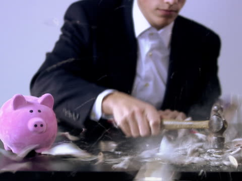 a man with two piggy banks in front of him he uses a hammer and breaks one of them sweden. - loss stock videos & royalty-free footage