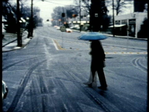 vidéos et rushes de 1975 ws man with umbrella walking across slushy street / united states / audio - météo