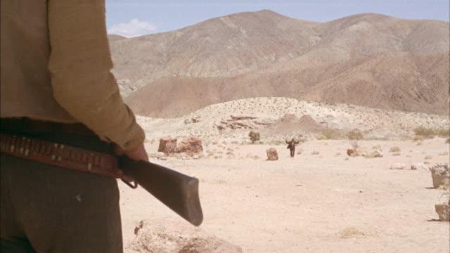 vidéos et rushes de ms man with uprising arms walking slowly toward  - armement
