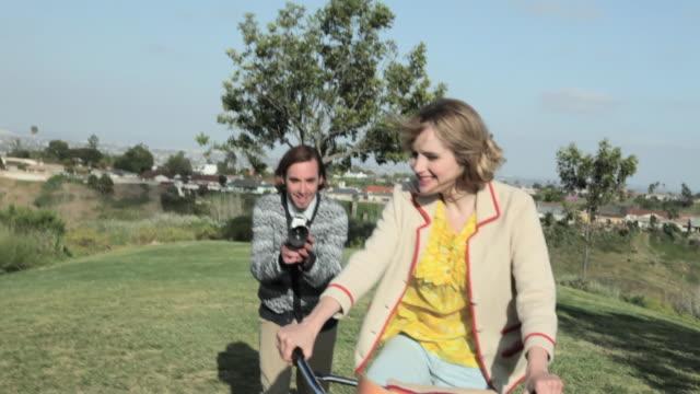 stockvideo's en b-roll-footage met man with video camera, following girlfriend as she cycles - jong van hart