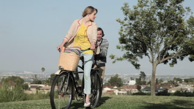 vidéos et rushes de man with video camera, following girlfriend as she cycles - jeune d'esprit