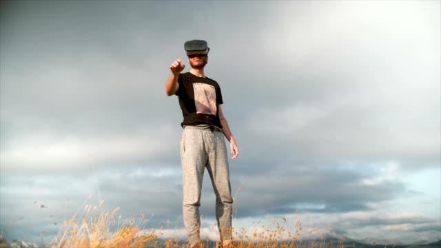 vídeos y material grabado en eventos de stock de man with virtual reality glasses over a mountain - realidad aumentada
