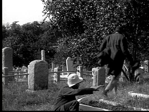 stockvideo's en b-roll-footage met 1916 b&w ms man with walking stick falling over as man in top hat runs to get out of graveyard/ man exiting cemetary gate and running in place  - mid volwassen mannen