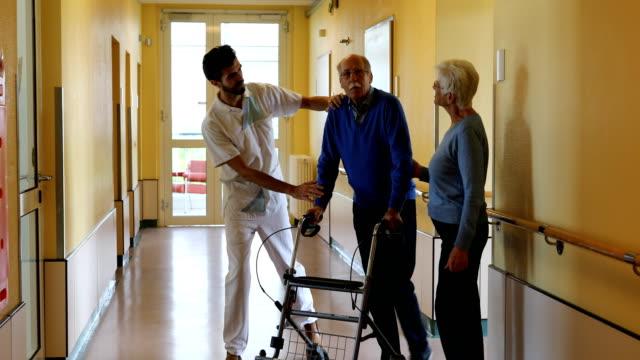 man med hustru och sjuksköterska gör walking övning i rehab - tyskland bildbanksvideor och videomaterial från bakom kulisserna