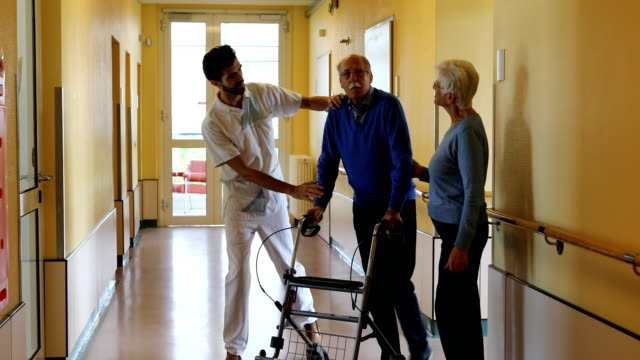 stockvideo's en b-roll-footage met man met vrouw en verpleegster doen wandelen oefening in rehab - germany