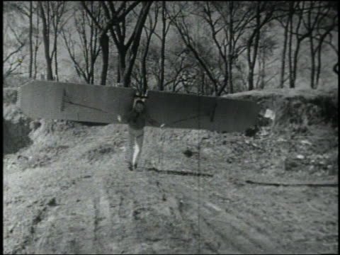 B/W man with wings on back running toward camera