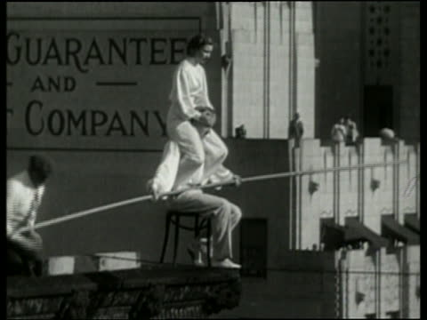 1936 B/W man with woman on shoulders sits on chair on tightrope / Los Angeles / NO AUDIO