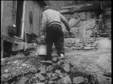 stockvideo's en b-roll-footage met b/w 1939 man with wooden leg carrying coal in bucket towards shack / documentary - grote depressie nieuwsevenement