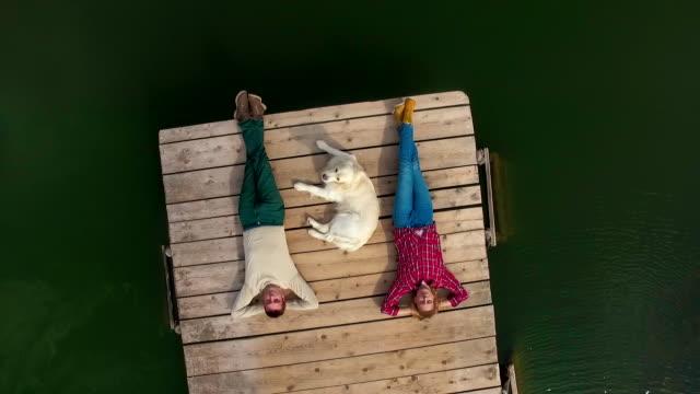 Mann, Frau und Hund liegend auf Pier am See