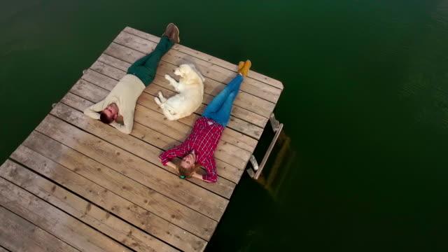 Man, woman and dog lying down on pier at lake