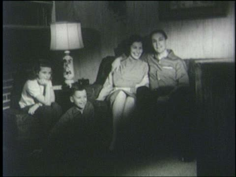 B/W 1952 man, woman, boy + girl sitting in living room watching television