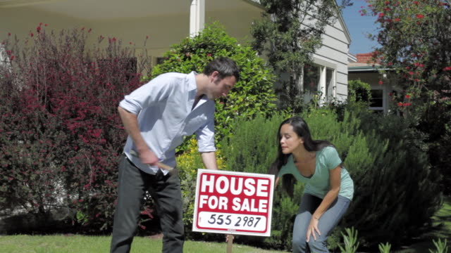 "ms man & woman carries out ""house for sale"" sign and planting into front lawn / santa monica, ca, united states - santa monica house stock videos & royalty-free footage"