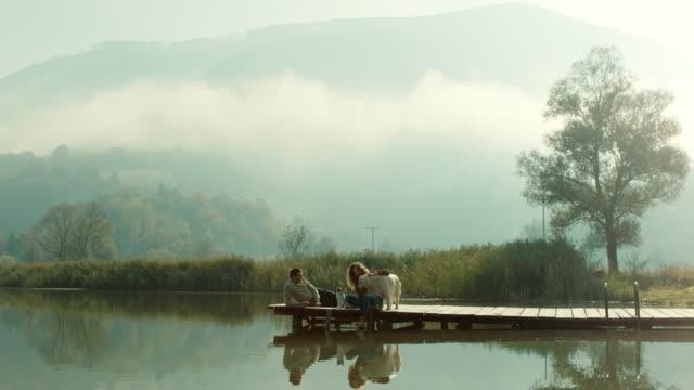 vídeos y material grabado en eventos de stock de hombre, mujer, gato y perro en el muelle en el lago - perro y gato