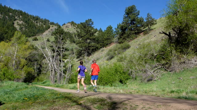 Man woman couple morning running Bear Creek Trail Colorado Rocky Mountains