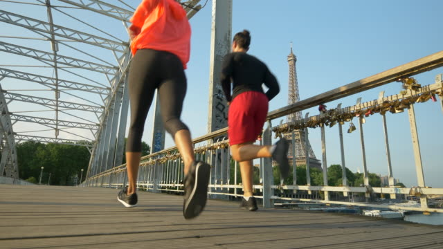 A man woman couple running across a bridge with the Eiffel Tower. - Slow Motion