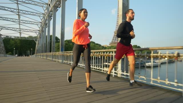 vidéos et rushes de a man woman couple running across a bridge with the eiffel tower. - slow motion - métis