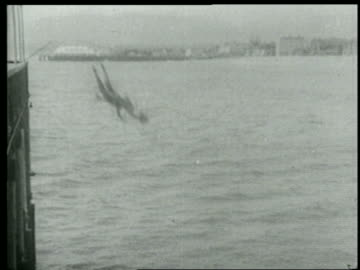 b/w 1915 man + woman falling from pier into water / short - slapstick comedy stock videos & royalty-free footage