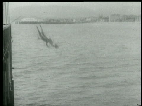 b/w 1915 man + woman falling from pier into water / short - slapstick stock videos & royalty-free footage