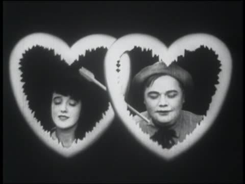 b/w 1916 man + woman framed by hearts with arrow thru them - fatty arbuckle stock videos and b-roll footage