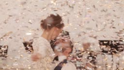 Man woman happy couple dance embracing under shining golden light confetti falling from above. Groom holds bride in hands twirling her celebrating festive mood music band playing live at background