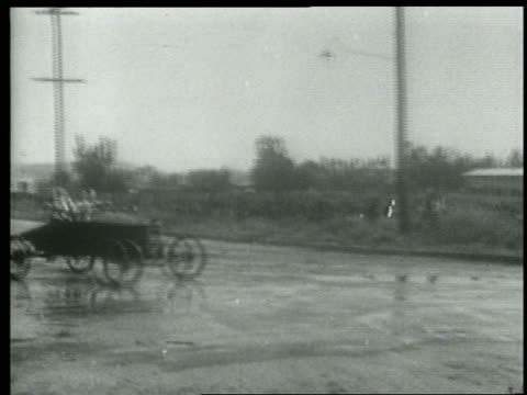 b/w 1915 man + woman in car skidding + spinning on wet road / short - 横滑り点の映像素材/bロール