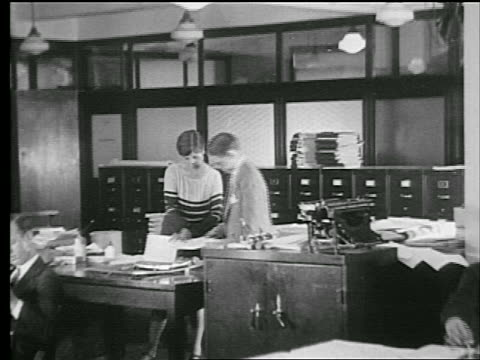 stockvideo's en b-roll-footage met b/w 1927 man + woman looking at papers together at desk in office / industrial - 1927