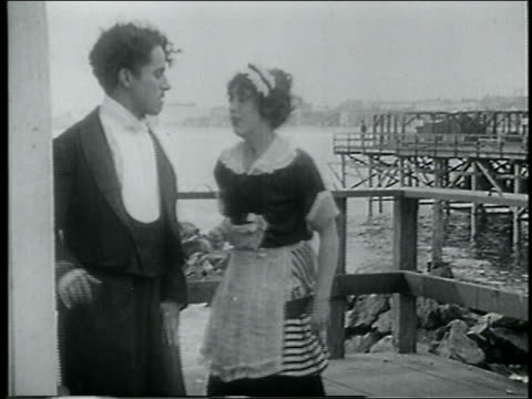 stockvideo's en b-roll-footage met b/w 1915 man woman on pier kicking each other in buttocks - 1915