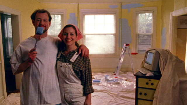 vídeos de stock e filmes b-roll de ms portrait man + woman posing in drop cloth covered room / man tries to paint woman's face - pano de protecção