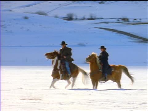 pan man + woman riding galloping horses through deep snow on plain / silverthorne, co - galoppieren stock-videos und b-roll-filmmaterial