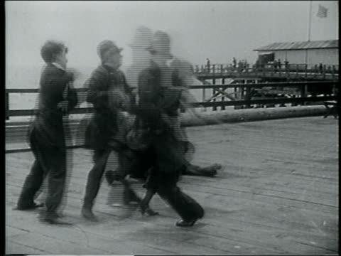 vídeos de stock, filmes e b-roll de b/w 1915 man + woman running directing bumbling keystone kops then running in opposite direction - charlie chaplin