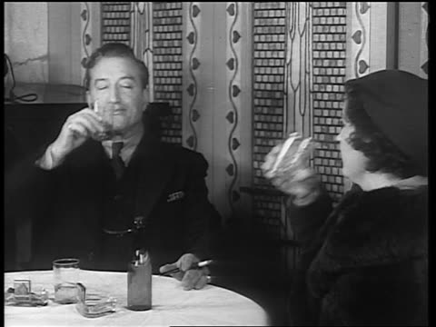 b/w 1933 man woman sitting at table drinking from glasses / end of prohibition - 1933年点の映像素材/bロール