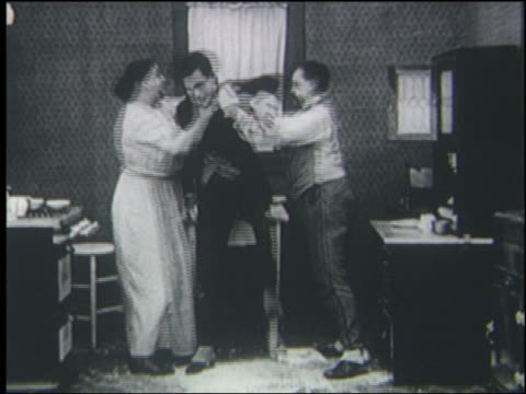 vidéos et rushes de b/w 1919 man woman slapping beating up another man in kitchen - 1910 1919