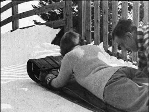 b/w 1924 man + woman starting off down hill on toboggan / lake placid / industrial - 1924 stock-videos und b-roll-filmmaterial